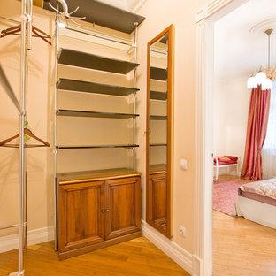 Klassisk inredning av ett mellanstort walk-in-closet för könsneutrala, med skåp i shakerstil, bruna skåp, mellanmörkt trägolv och brunt golv