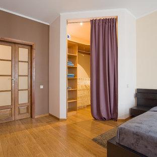 Imagen de armario vestidor unisex, actual, de tamaño medio, con armarios abiertos, puertas de armario marrones, suelo laminado y suelo marrón