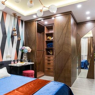 Идея дизайна: гардеробная комната в современном стиле с плоскими фасадами и фасадами цвета дерева среднего тона