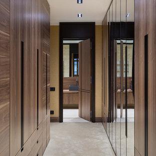 モスクワの広い男女兼用コンテンポラリースタイルのおしゃれなウォークインクローゼット (フラットパネル扉のキャビネット、中間色木目調キャビネット、カーペット敷き、ベージュの床) の写真