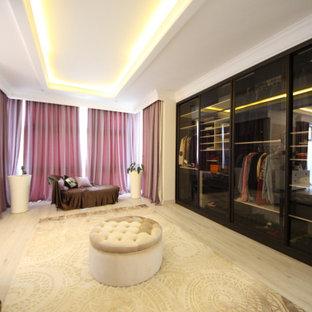 Foto de armario de hombre, bohemio, de tamaño medio, con armarios tipo vitrina, puertas de armario marrones, suelo de madera en tonos medios y suelo beige