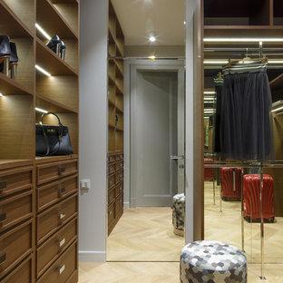 На фото: гардеробная комната унисекс в стиле современная классика с фасадами с утопленной филенкой, фасадами цвета дерева среднего тона и светлым паркетным полом с