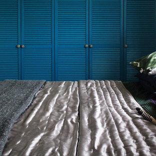 Ejemplo de armario y vestidor unisex, mediterráneo, con suelo de madera oscura y armarios con puertas mallorquinas