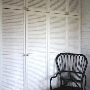 Diseño de armario y vestidor unisex con suelo de madera oscura y armarios con puertas mallorquinas