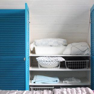 Modelo de armario y vestidor unisex, mediterráneo, con suelo de madera oscura y armarios con puertas mallorquinas