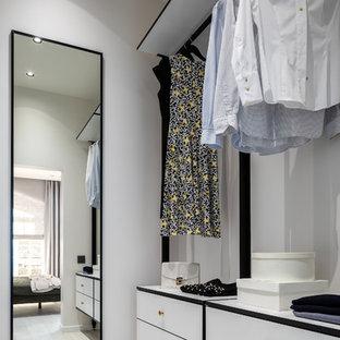 Imagen de armario vestidor unisex, contemporáneo, pequeño, con armarios con paneles lisos, puertas de armario blancas, suelo laminado y suelo beige