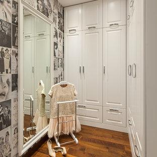 Идея дизайна: гардеробная комната в стиле современная классика с белыми фасадами, паркетным полом среднего тона и коричневым полом для женщин