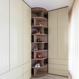 Cette image montre un dressing design de taille moyenne pour une femme avec un placard à porte plane, des portes de placard beiges, un sol en carrelage de porcelaine et un sol beige.