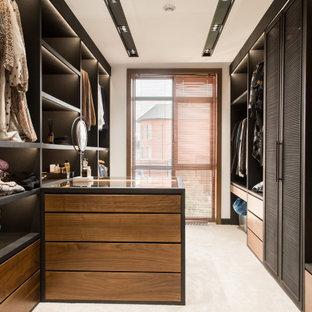Ispirazione per uno spazio per vestirsi unisex contemporaneo con ante a persiana, ante nere e pavimento beige