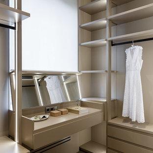 Foto de vestidor de mujer, actual, con armarios abiertos, puertas de armario marrones, suelo de madera oscura y suelo marrón