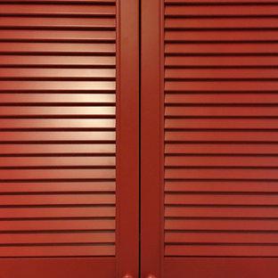 Modelo de armario actual, grande, con armarios con puertas mallorquinas, puertas de armario rojas, suelo de baldosas de cerámica y suelo marrón