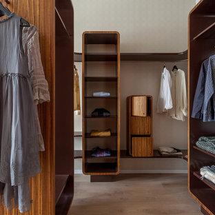 Стильный дизайн: гардеробная унисекс в современном стиле с открытыми фасадами, фасадами цвета дерева среднего тона, светлым паркетным полом и бежевым полом - последний тренд