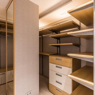 На фото: гардеробная комната унисекс в современном стиле с светлым паркетным полом, бежевым полом и открытыми фасадами с