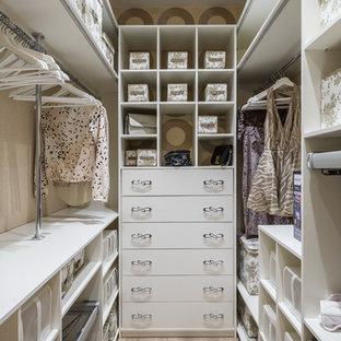 Foto de armario vestidor de mujer, contemporáneo, pequeño, con armarios con paneles lisos, puertas de armario blancas, suelo de madera clara y suelo beige