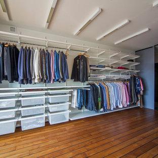 На фото: огромная гардеробная комната в современном стиле с открытыми фасадами, темным паркетным полом, коричневым полом и белыми фасадами для мужчин с
