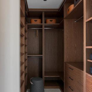 Пример оригинального дизайна: гардеробная комната среднего размера, унисекс в современном стиле с плоскими фасадами, фасадами цвета дерева среднего тона и белым полом