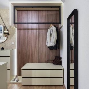 Imagen de vestidor unisex, actual, con armarios con paneles lisos, puertas de armario blancas, suelo de madera en tonos medios y suelo marrón
