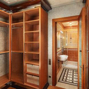 Aménagement d'un grand dressing victorien neutre avec un placard sans porte et un sol orange.