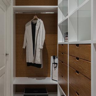 Modelo de armario vestidor unisex, contemporáneo, de tamaño medio, con armarios con paneles lisos, suelo de corcho, puertas de armario de madera oscura y suelo beige