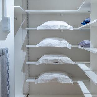 Diseño de armario vestidor unisex, contemporáneo, pequeño, con suelo de madera en tonos medios, armarios abiertos, puertas de armario blancas y suelo marrón