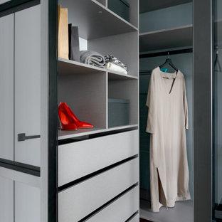 Imagen de armario vestidor unisex, actual, de tamaño medio, con armarios con paneles lisos, puertas de armario grises, suelo laminado y suelo beige
