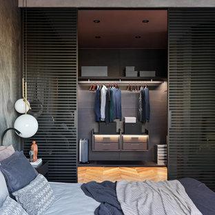 Modelo de armario y vestidor de hombre, actual, de tamaño medio, con armarios con paneles lisos, puertas de armario grises, suelo de madera en tonos medios y suelo marrón