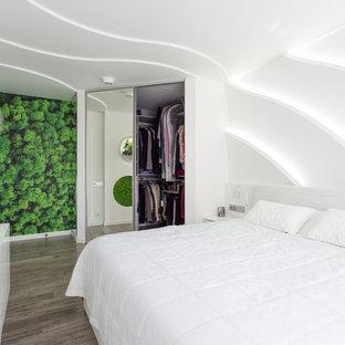 Immagine di una cabina armadio unisex minimal di medie dimensioni con ante di vetro, pavimento in bambù e pavimento grigio