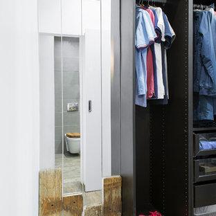 Imagen de armario vestidor de hombre, industrial, pequeño, con armarios con paneles lisos, puertas de armario de madera en tonos medios, suelo laminado y suelo marrón