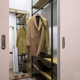 Foto di una piccola cabina armadio per uomo industriale con pavimento in laminato, nessun'anta e pavimento marrone