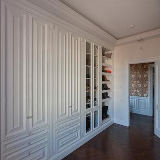 Источник вдохновения для домашнего уюта: гардеробная комната унисекс в классическом стиле с фасадами с выступающей филенкой, белыми фасадами, темным паркетным полом и коричневым полом