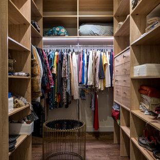Ejemplo de armario vestidor de mujer, ecléctico, de tamaño medio, con armarios abiertos, puertas de armario de madera oscura, suelo de madera oscura y suelo marrón