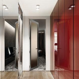 Modelo de armario vestidor unisex, contemporáneo, con armarios con paneles lisos, puertas de armario rojas, suelo de madera clara y suelo beige