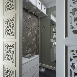 Small transitional gender-neutral walk-in wardrobe in Moscow with flat-panel cabinets, white cabinets, dark hardwood floors and black floor.