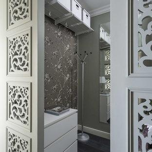 Стильный дизайн: маленькая гардеробная комната унисекс в стиле современная классика с плоскими фасадами, белыми фасадами, темным паркетным полом и черным полом - последний тренд
