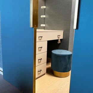 Ejemplo de armario vestidor unisex, contemporáneo, pequeño, con armarios con paneles lisos, puertas de armario beige, suelo de madera en tonos medios y suelo beige