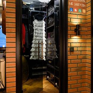 Стильный дизайн: маленькая гардеробная комната унисекс в стиле лофт с черными фасадами, открытыми фасадами и коричневым полом - последний тренд