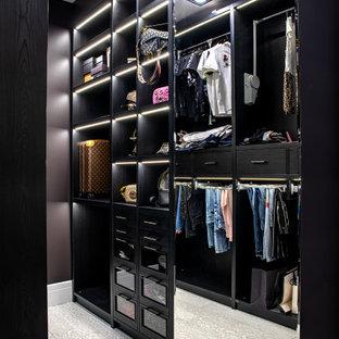 Пример оригинального дизайна: гардеробная комната в стиле современная классика с черными фасадами и серым полом