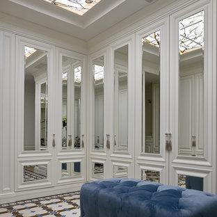 モスクワの男女兼用トランジショナルスタイルのおしゃれなウォークインクローゼット (ガラス扉のキャビネット、白いキャビネット、マルチカラーの床) の写真