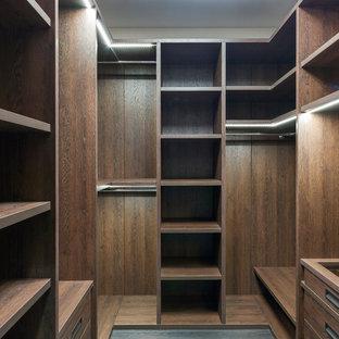 На фото: гардеробная комната унисекс в современном стиле с открытыми фасадами, темными деревянными фасадами и темным паркетным полом