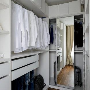 Neutraler Moderner Begehbarer Kleiderschrank mit flächenbündigen Schrankfronten, weißen Schränken, dunklem Holzboden und braunem Boden in Moskau