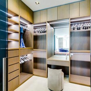 Ejemplo de vestidor actual con puertas de armario beige y suelo blanco