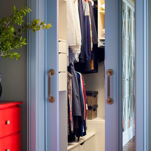 Imagen de armario vestidor unisex, tradicional renovado, con armarios con paneles lisos, puertas de armario blancas y suelo de madera oscura