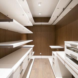 Foto di una cabina armadio unisex contemporanea con ante lisce, ante bianche, parquet chiaro e pavimento beige