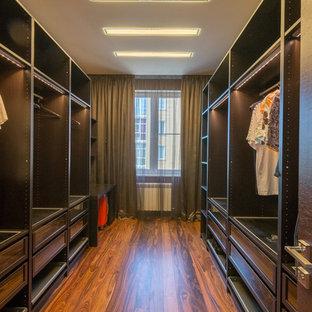 Ejemplo de armario vestidor de hombre, actual, grande, con suelo de madera en tonos medios y puertas de armario de madera en tonos medios