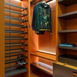 Modelo de armario vestidor unisex, actual, con armarios abiertos, puertas de armario grises, suelo de madera en tonos medios y suelo marrón