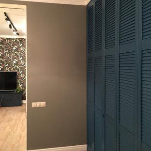 Imagen de armario vestidor escandinavo, grande, con armarios con puertas mallorquinas, puertas de armario azules, suelo laminado y suelo beige