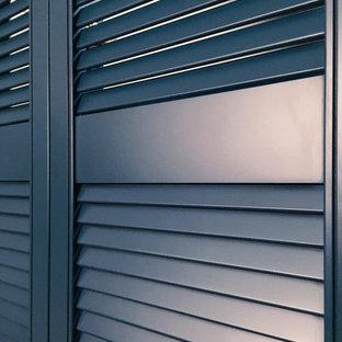 Esempio di una grande cabina armadio nordica con ante a persiana, ante blu, pavimento in laminato e pavimento beige