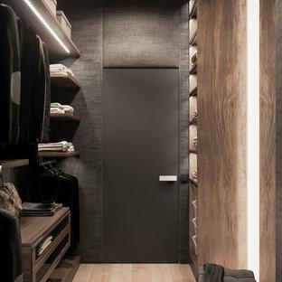 Ejemplo de armario vestidor unisex, nórdico, de tamaño medio, con armarios con paneles lisos, puertas de armario de madera oscura, suelo de madera clara y suelo beige