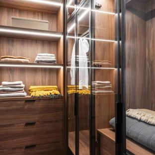 Ejemplo de armario vestidor unisex, actual, pequeño, con armarios tipo vitrina, puertas de armario de madera oscura, moqueta y suelo multicolor
