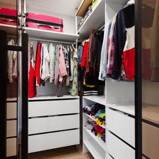 Ejemplo de armario vestidor unisex, actual, pequeño, con armarios tipo vitrina, puertas de armario marrones, suelo laminado y suelo beige